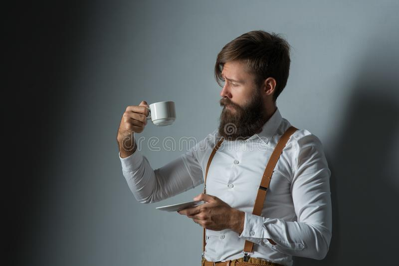 Young handsome man with a beard. In a white shirt and yellow suspenders with cup coffee or tea on a gray background stock photo