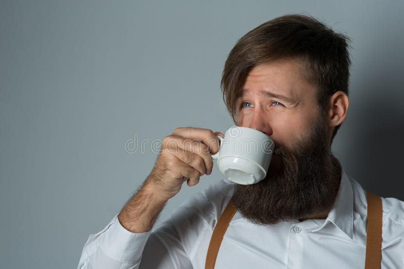 Young handsome man with a beard. In a white shirt and yellow suspenders with cup coffee or tea on a gray background stock photography