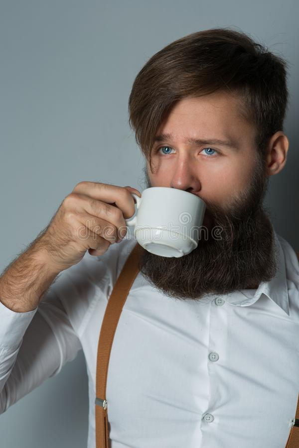 Young handsome man with a beard. In a white shirt and yellow suspenders with cup coffee or tea on a gray background stock images