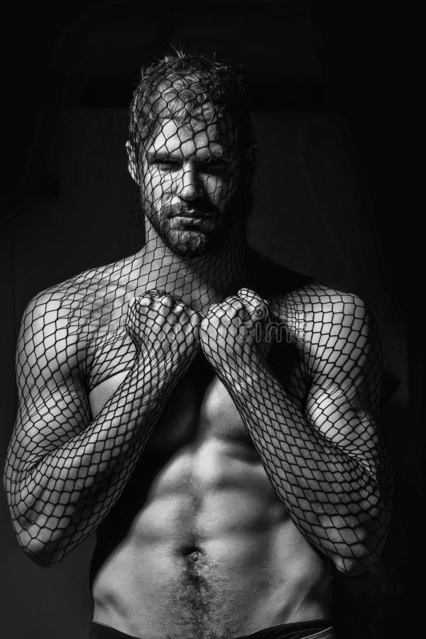 Man robber wears mask. Young handsome man bearded guy with beard or robber bandit gangster wears mask of black fishnet stocking on face on dark background with stock image