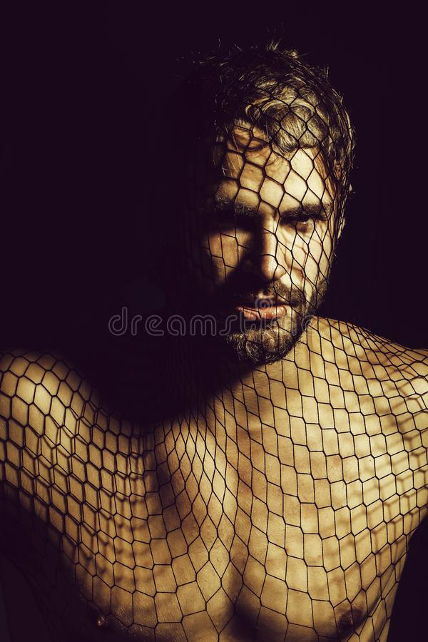 Man robber wears mask. Young handsome man bearded guy with beard or robber bandit gangster wears mask of black fishnet stocking on face on dark background with stock images