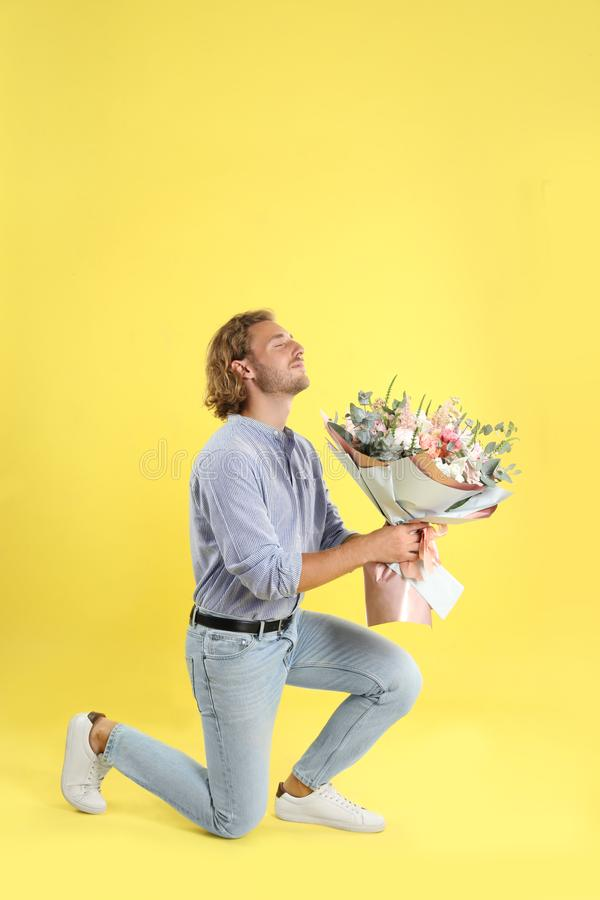 Young handsome man with beautiful flower bouquet bending knee stock photos