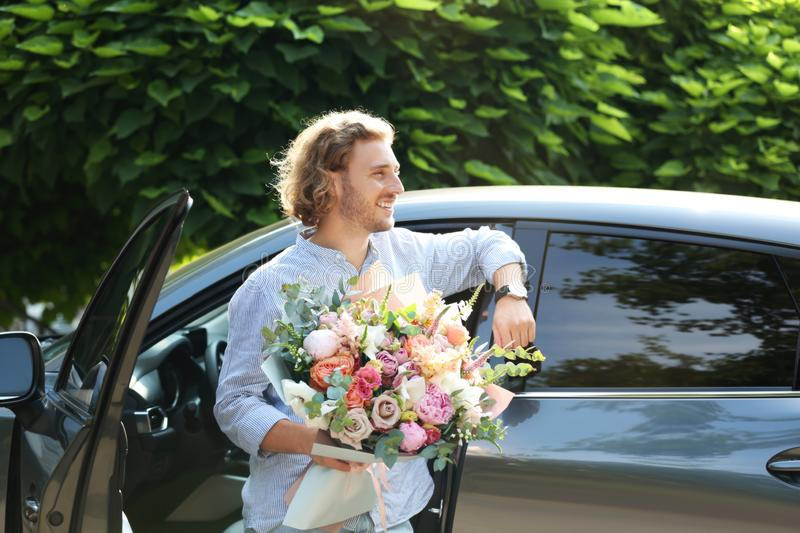 Young handsome man with beautiful flower bouquet near car royalty free stock images