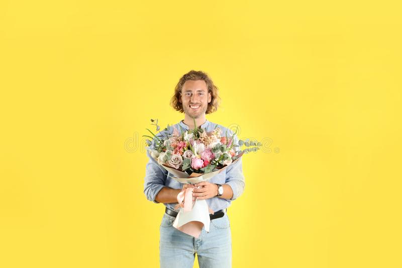 Young handsome man with beautiful flower bouquet royalty free stock image