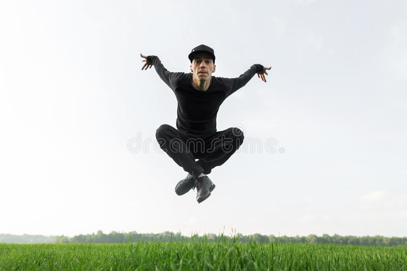 Young handsome man in black fashionable clothes in a stylish cap in trendy sneakers jumping on a background of green grass. And blue sky. Attractive guy dancer royalty free stock image