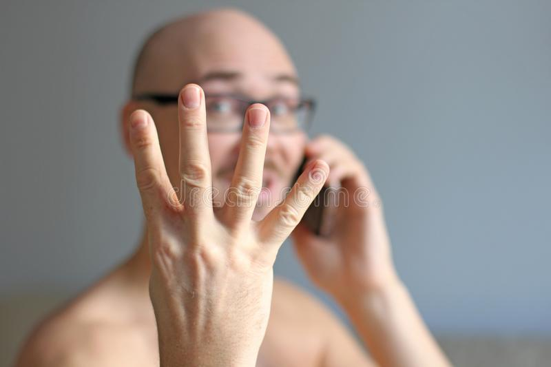 Young handsome man in black glasses is talking on the phone. Closeup portrait of a man. A man shows four fingers. Everything is royalty free stock image