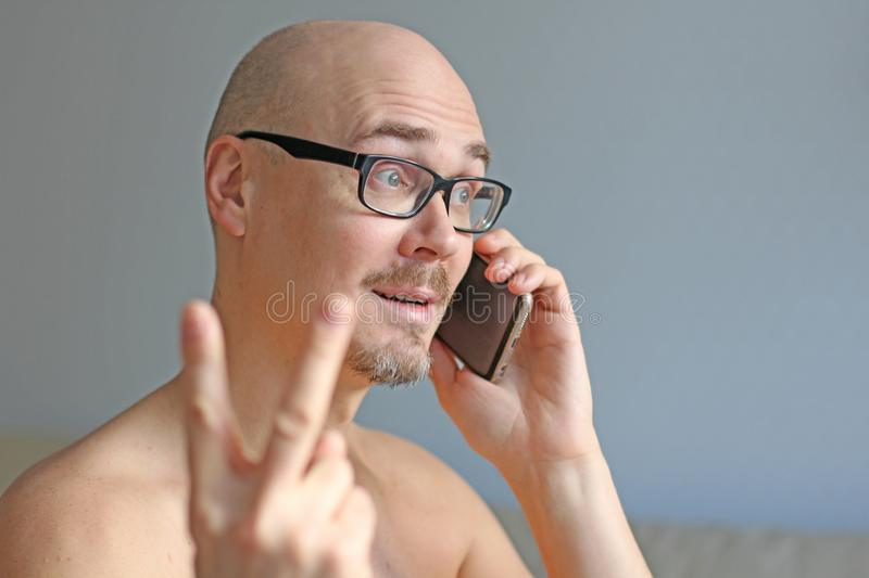 Young handsome man in black glasses is talking on the phone. Closeup portrait of a man. A man shows a sign of victory. Everything royalty free stock photo