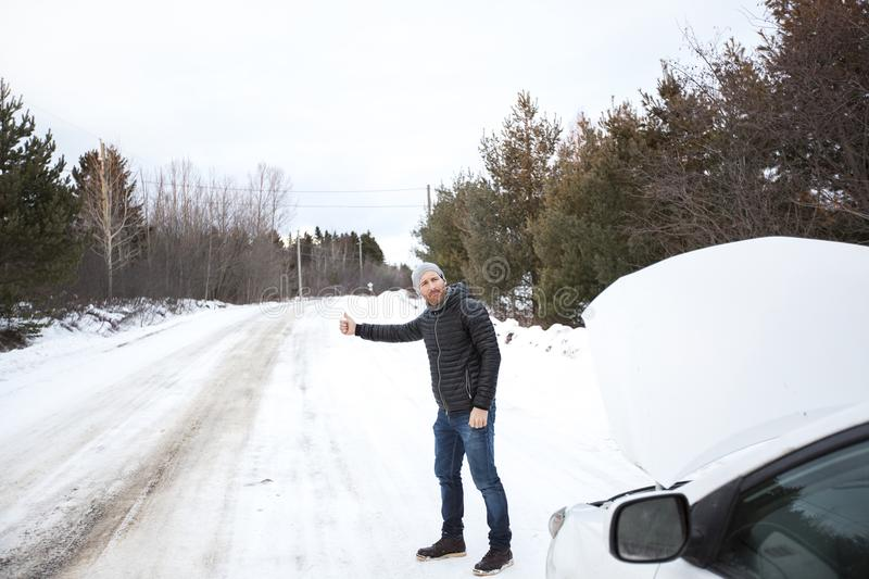 Young handsome man in black jacket in winter, stood on the highway and hitchhiking. A young handsome man in black jacket in winter, stood on the highway and stock image