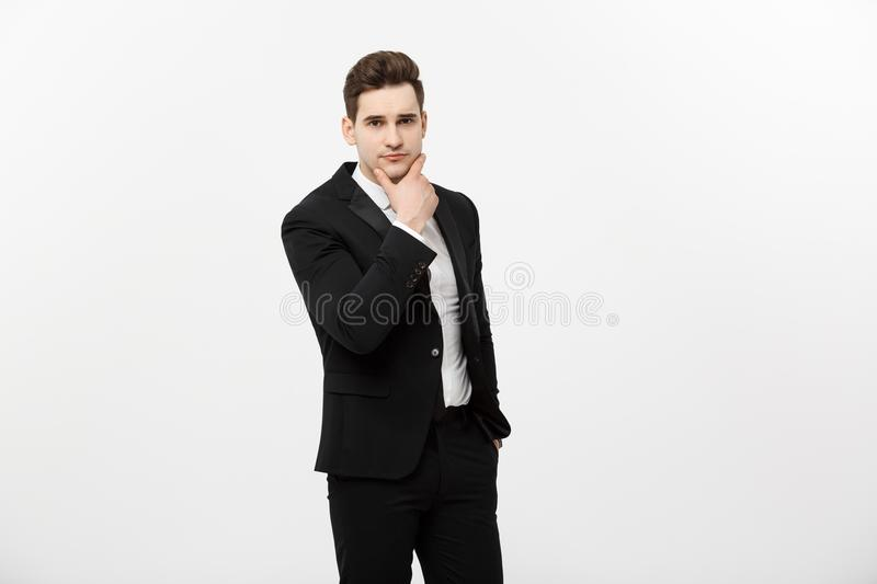 Young handsome man in black suit and glasses looking at copy-space thinking or dreaming isolated over white background royalty free stock photos