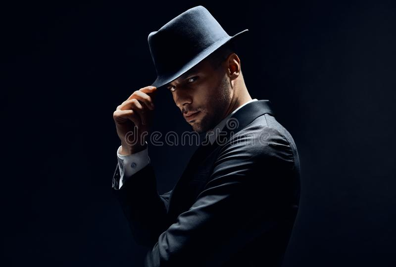 Young handsome man in black suit touch his hat on dark background stock photo