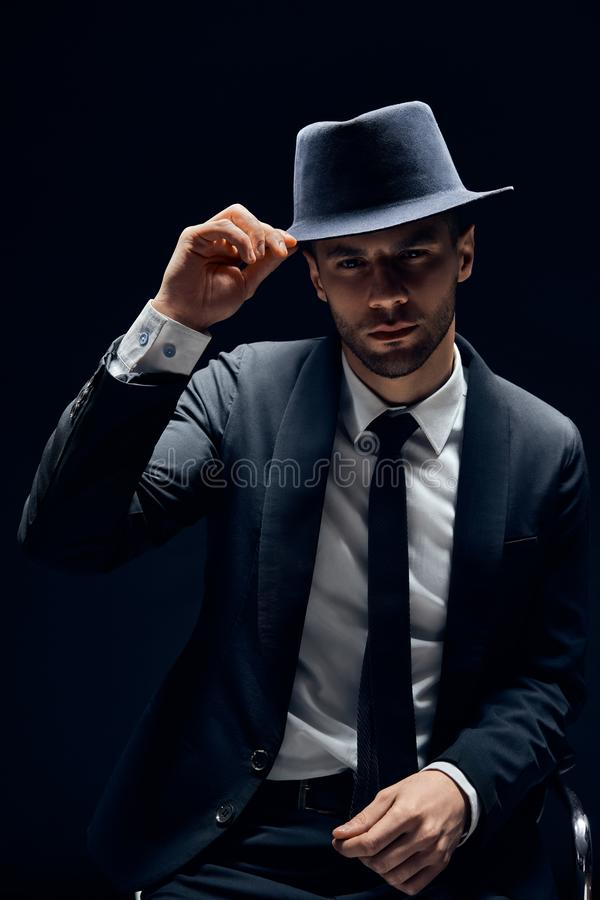 Young handsome man in black suit touch his hat on dark background stock image
