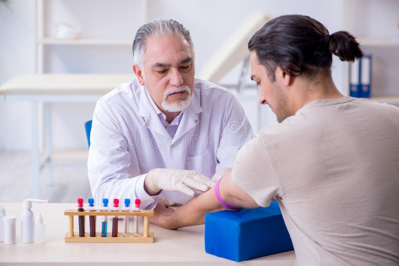 Young handsome man during blood test sampling procedure stock photo