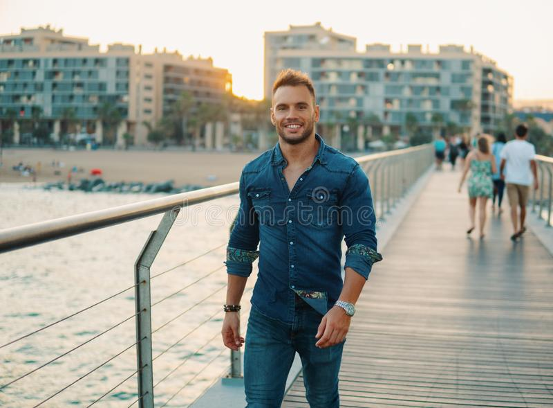 A young handsome man on the bridge near beautiful beach. stock photos