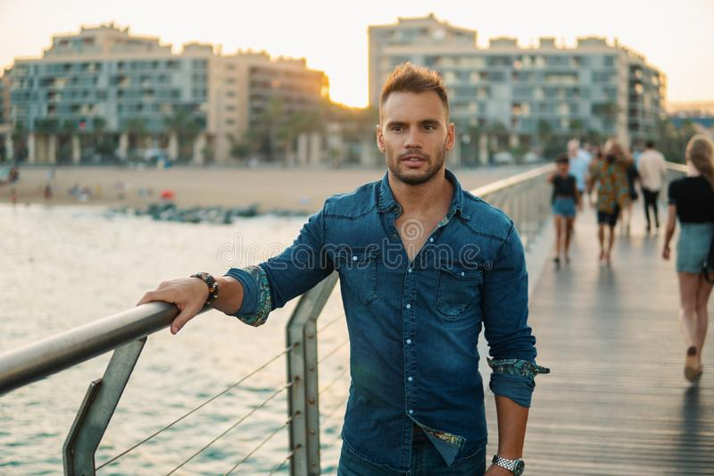 A young handsome man on the bridge near beautiful beach. stock photography