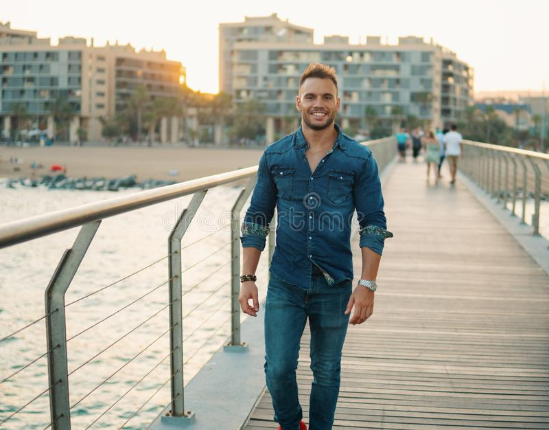 A young handsome man on the bridge near beautiful beach. royalty free stock images