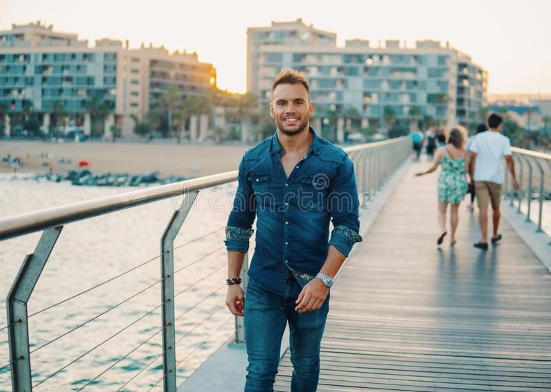 A young handsome man on the bridge near beautiful beach. royalty free stock photos