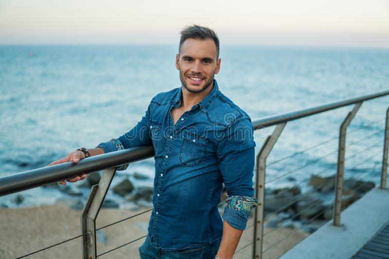 A young handsome man on the bridge near beautiful beach. stock photo