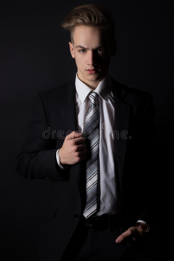 Young handsome man in a business suit and a white shirt and tie in formal style in the Studio on a black background royalty free stock photo