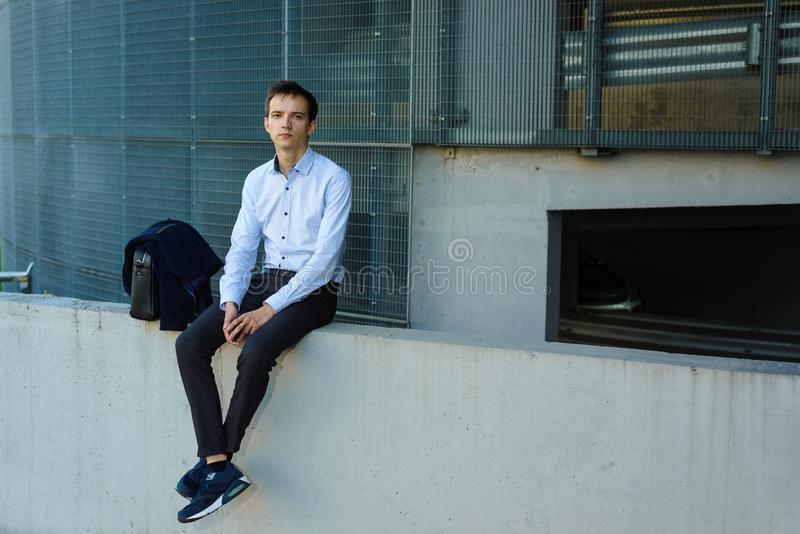 Young handsome man businessman sitting near building stock image