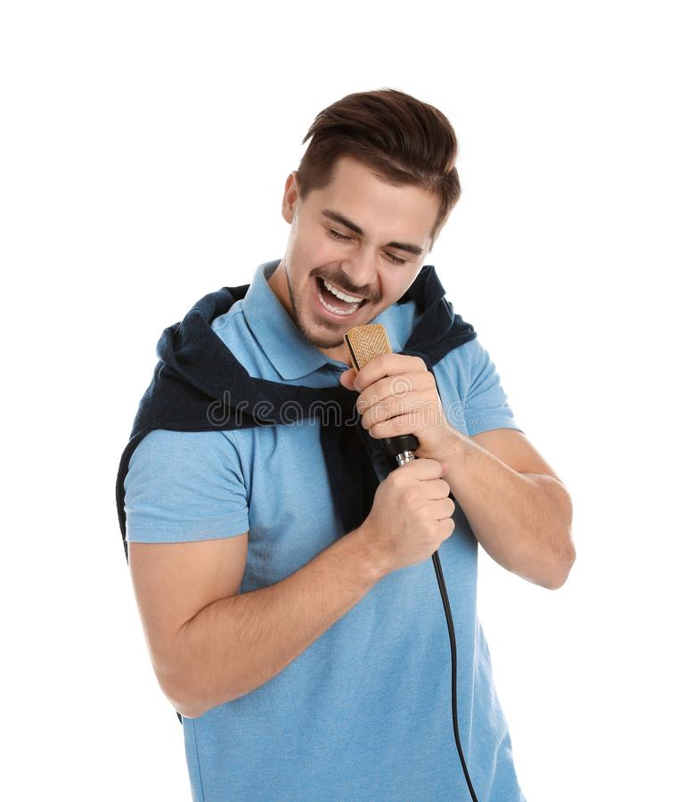 Young handsome man in casual clothes singing with microphone. On white background royalty free stock images