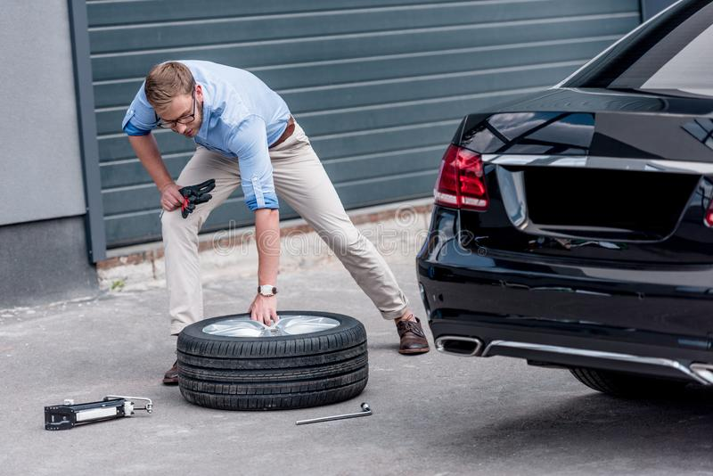 Young handsome man changing car. Tire royalty free stock images