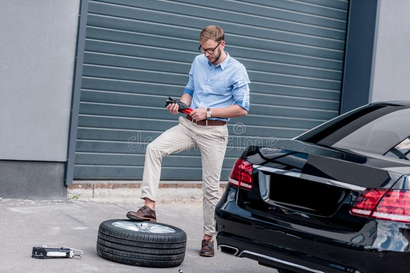 Young handsome man changing car. Tire stock images