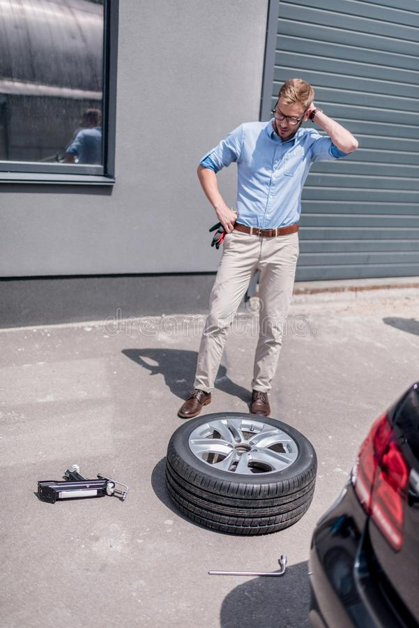 Young handsome man changing car. Tire royalty free stock image
