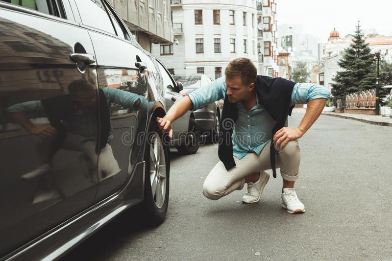 Young handsome man checking wheel of his car having problems on the road royalty free stock photos