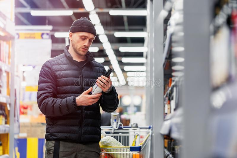 Young handsome man choosing wine in supermarket. Matter of wine choice stock photography