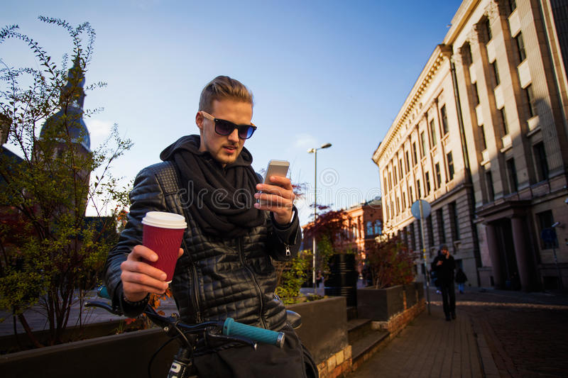 Young and handsome man in the city having coffee and using smartphone stock photos
