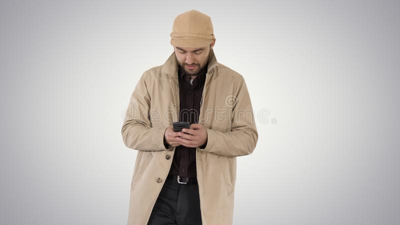 Young handsome man in cloak messaging with phone on gradient background. stock photography