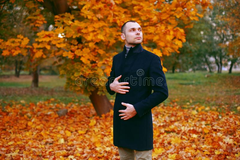 Young handsome man in coat. Fashionable well dressed man posing in stylish coat. Confident and focused boy outdoor at autumn. royalty free stock images