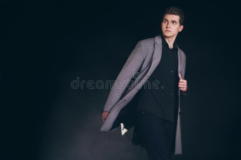 Young handsome man in coat. Portrait of fashionable well dressed man posing in grey stylish coat. Confident and focused boy royalty free stock images