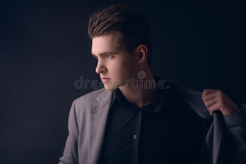 Young handsome man in coat. Portrait of fashionable well dressed man posing in grey stylish coat. Confident and focused boy stock photography