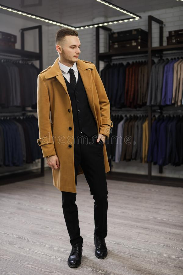 Young handsome man in coat in suit shop royalty free stock photos