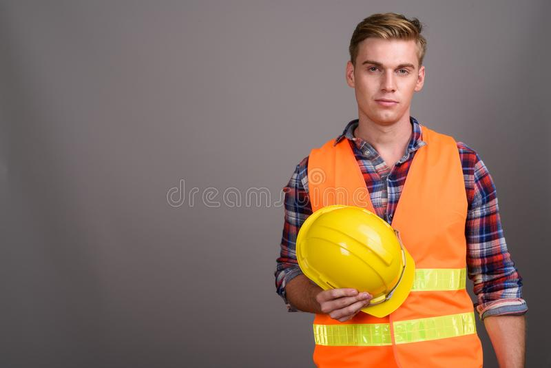 Young handsome man construction worker with blond hair against g stock image
