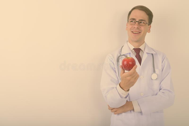 Young handsome man doctor wearing eyeglasses against white background stock images