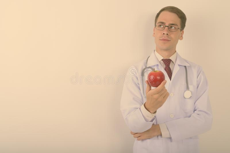 Young handsome man doctor wearing eyeglasses against white background royalty free stock photos