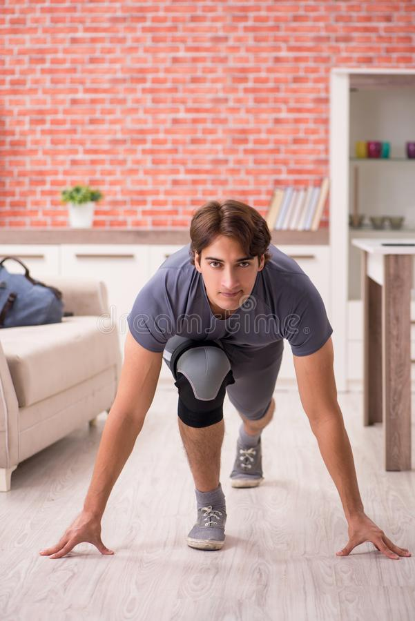 The young handsome man doing sport exercises at home royalty free stock image
