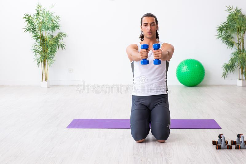Young handsome man doing sport exercises indoors. The young handsome man doing sport exercises indoors stock photos