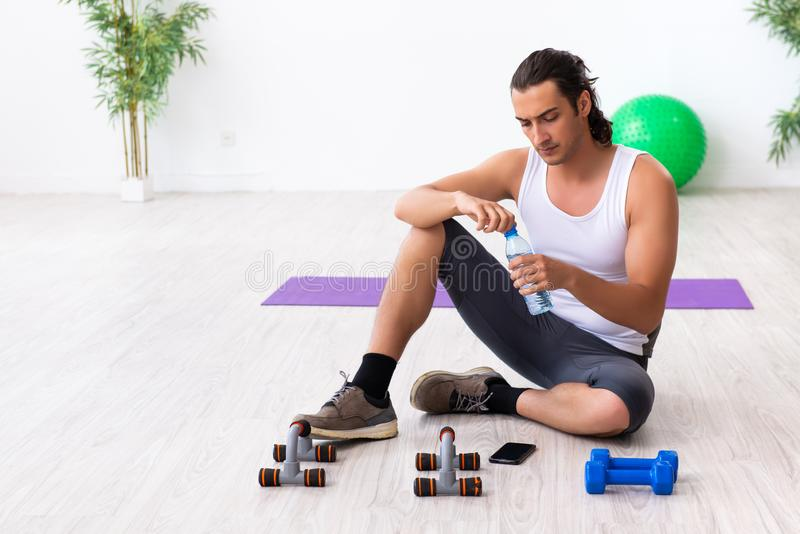 Young handsome man doing sport exercises indoors. The young handsome man doing sport exercises indoors royalty free stock photos