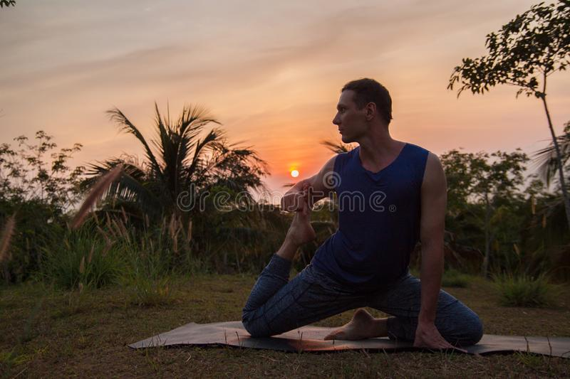 Young man doing yoga near the palm tree at sunset. stock photos