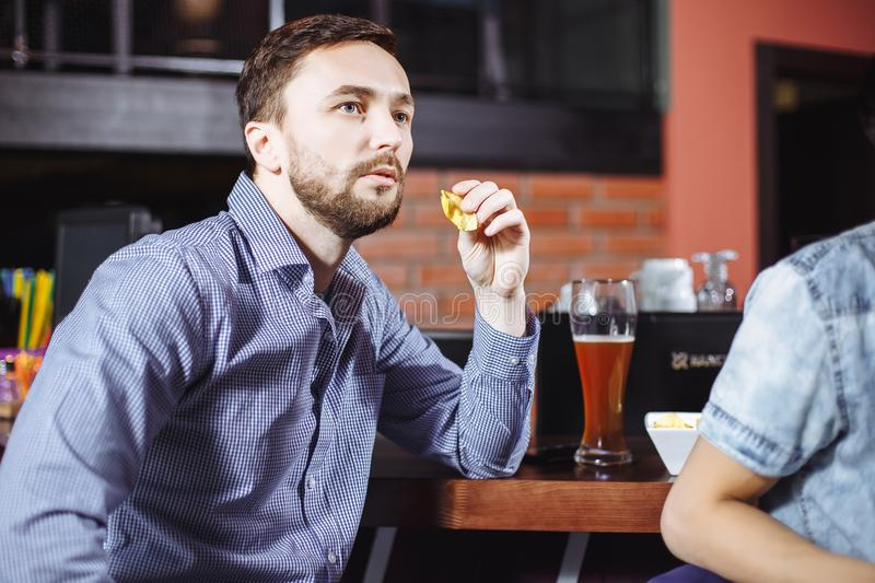 Young handsome man drinking beer and watching the game on TV in the bar stock photo