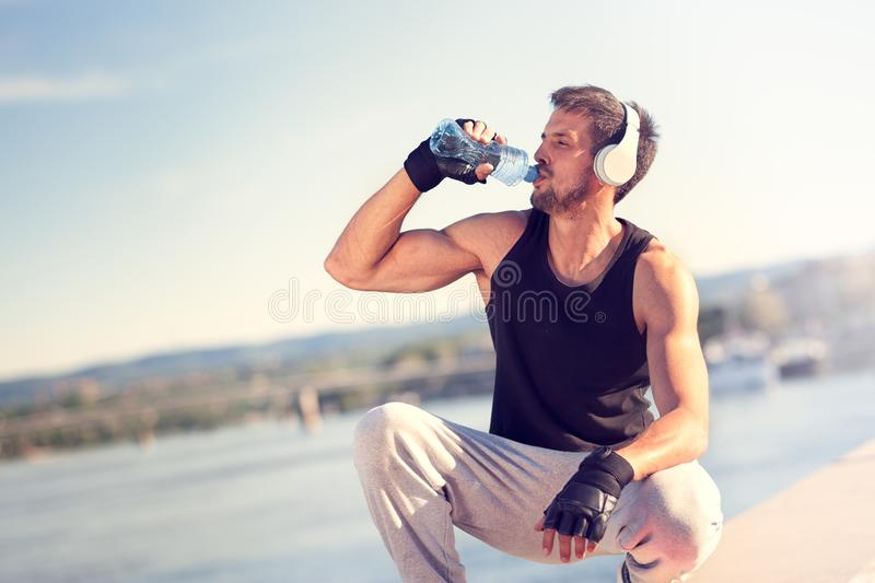 Trusty sporty man. Young handsome man drinking water after training hard. Man refreshing on break after doing sports outside. Outdoors recreation, stretching and stock images