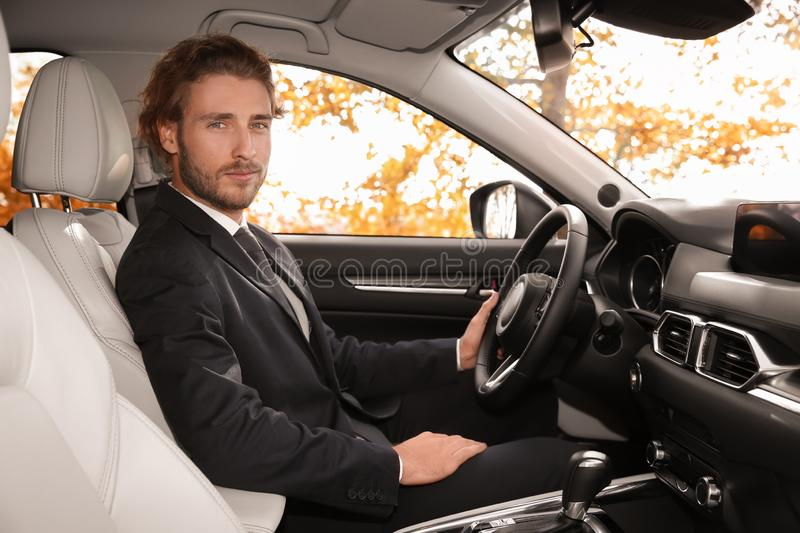Young handsome man in driver`s seat stock photo