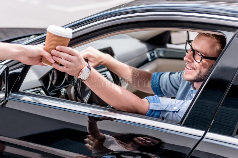 Young handsome man driving car and taking. Away coffee stock images