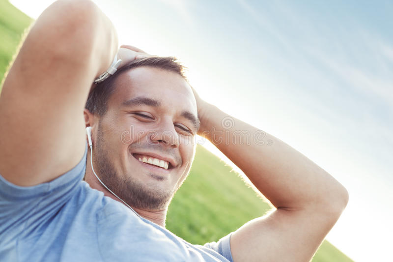Young and handsome man with earplugs lying in the park royalty free stock image