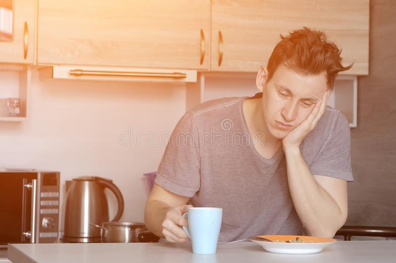 Young handsome man eating oatmeal porridge in the kitchen royalty free stock photos