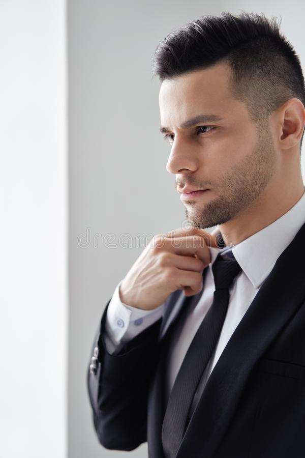 Young handsome man in elegant suit adjust his necktie stock photography