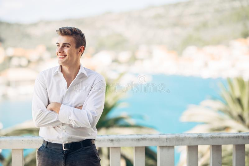 Young handsome man enjoying stay at luxury resort hotel with panoramic view on the sea royalty free stock images